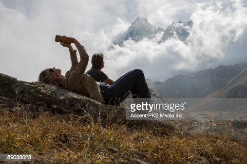 Woman uses digital tablet, man looks off, mountain : Stock Photo