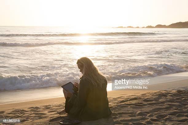 Woman uses digital tablet near edge of surf
