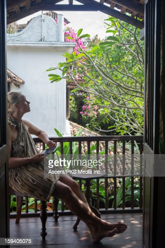 Woman uses digital tablet on outdoor veranda : Stock Photo