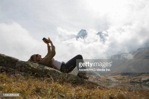 Woman uses digital tablet, on rock in mtn meadow : Stock Photo