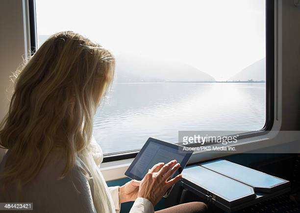 Woman uses digital tablet while riding on train