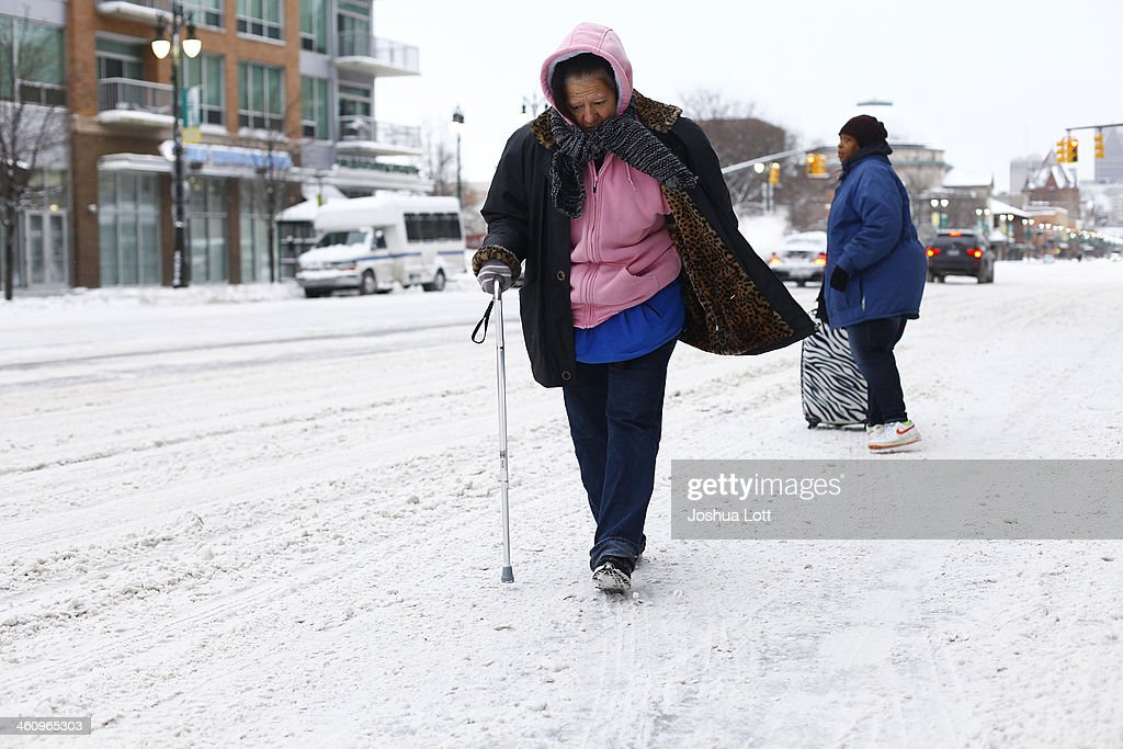 A woman uses her cane to navigate through several inches of snow along Woodward Avenue as the area deals with record breaking freezing weather January 6, 2014 in Detroit, Michigan. Michigan and most of the Midwest received their first major snow storm of 2014 last week and subzero temperatures are expected most of this week with wind-chill driving temperatures down to 50-70 degrees below zero. A 'polar vortex' weather pattern is bringing some of the coldest weather the U.S. has had in almost 20 years.