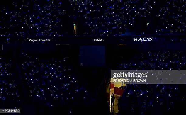 A woman uses her cellphone to take a picture as the audience watches a demonstration of the game 'Halo' at the Xbox media briefing where new games...