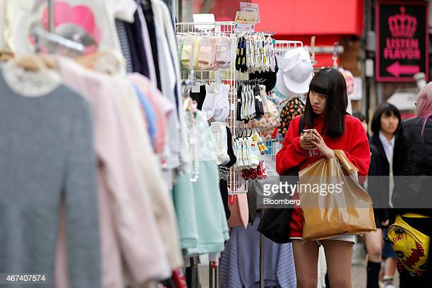 A woman uses her mobile device outside a clothing store on Takeshita Street in the Harajuku district of Tokyo Japan on Monday March 23 2015 Bank of...