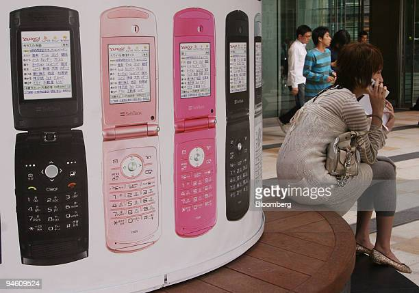 A woman uses her mobile phone as she sits by a pillar covered in Softbank Corp advertising in Tokyo Japan on Monday May 7 2007 Softbank Corp Japan's...