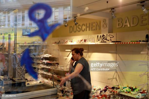 A woman uses her mobile phone as she stands in a looted Budnikowsky drugstore in Hamburg's Schanzenviertel district on July 8 2017 in Hamburg...