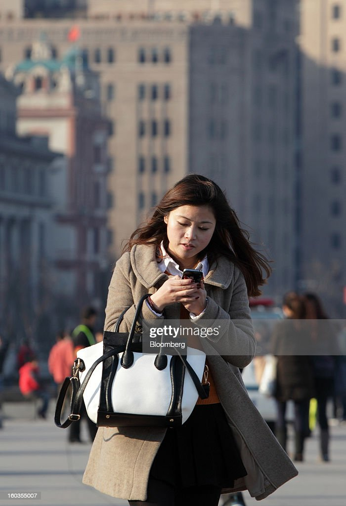 A woman uses her mobile phone as she walks along the Bund in Shanghai, China, on Monday, Jan. 28, 2013. China's economic growth accelerated for the first time in two years as government efforts to revive demand drove a rebound in industrial output, retail sales and the housing market. Photographer: Tomohiro Ohsumi/Bloomberg via Getty Images