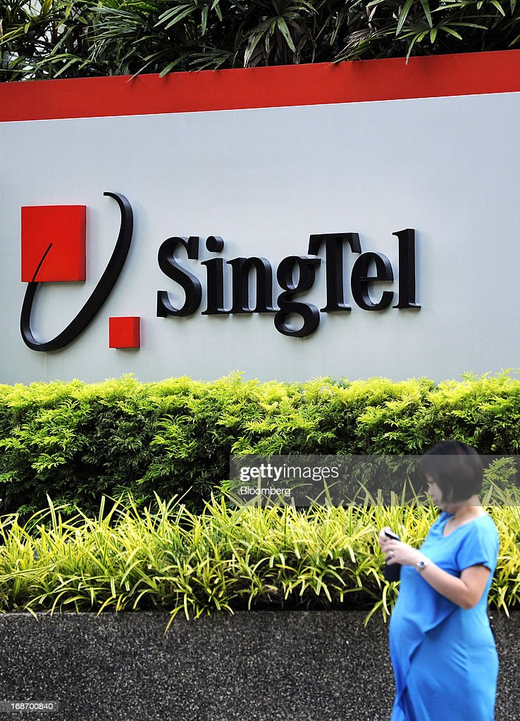 A woman uses her mobile phone as she walks past signage for Singapore Telecommunications Ltd. (SingTel) outside the company's headquarters in Singapore, on Monday, May 13, 2013. SingTel, southeast Asia's largest phone company, is scheduled to release fourth-quarter earnings on May 15. Photographer: Munshi Ahmed/Bloomberg via Getty Images