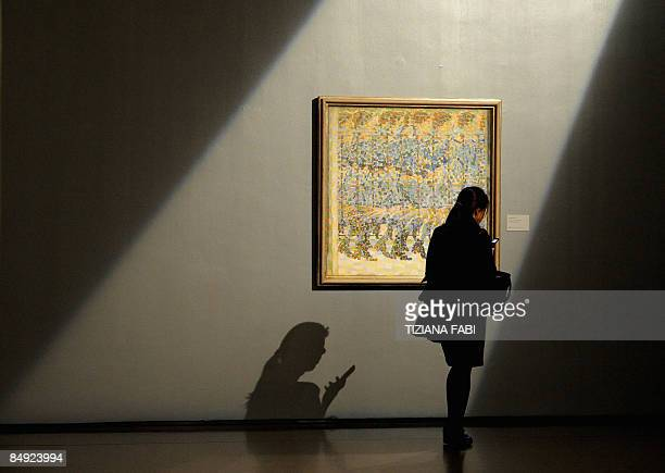 A woman uses her mobile phone by Italian artist Giacomo Balla's painting 'Girl Running on a Balcony ' on show at the opening of a new exhibition on...