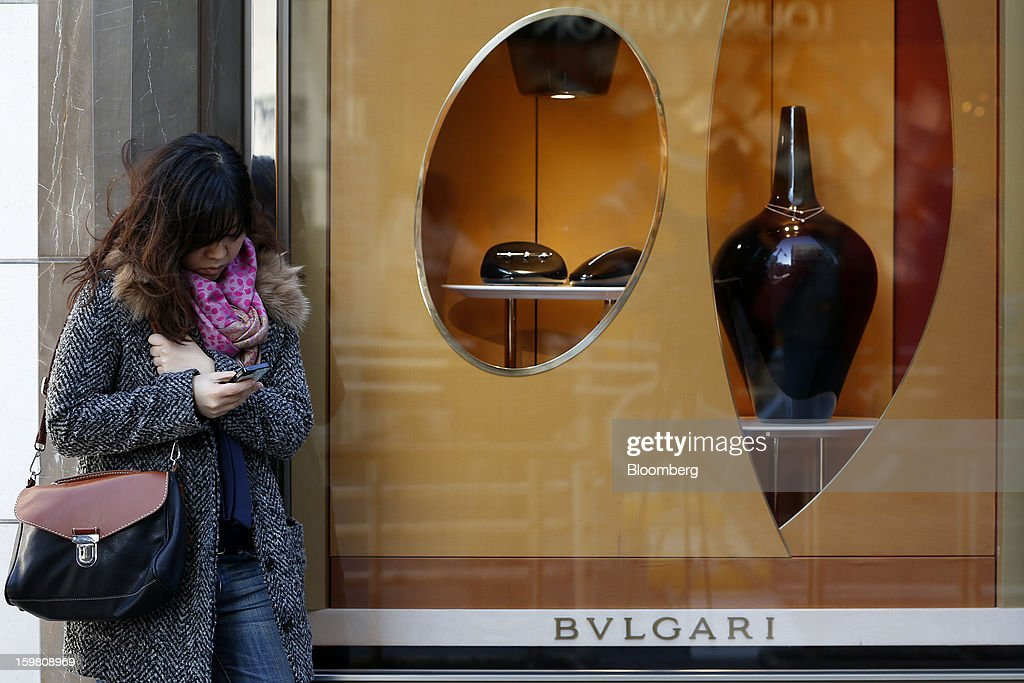 A woman uses her mobile phone outside a Bulgari SpA store, a luxury unit of LVMH Moet Hennessy Louis Vuitton SA, in the Ginza district of Tokyo, Japan, on Sunday, Jan. 20, 2013. Japan's consumer prices excluding fresh food, a benchmark monitored by the central bank, haven't advanced 2 percent for any year since 1997, when a national sales tax was increased. Photographer: Kiyoshi Ota/Bloomberg via Getty Images