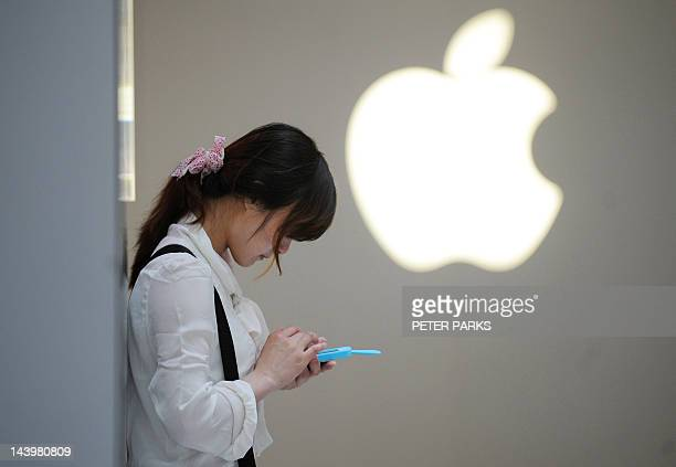 A woman uses her mobile phone outside an Apple store in Shanghai on May 7 2012 A Chinese computer company which sued Apple over the rights to the...