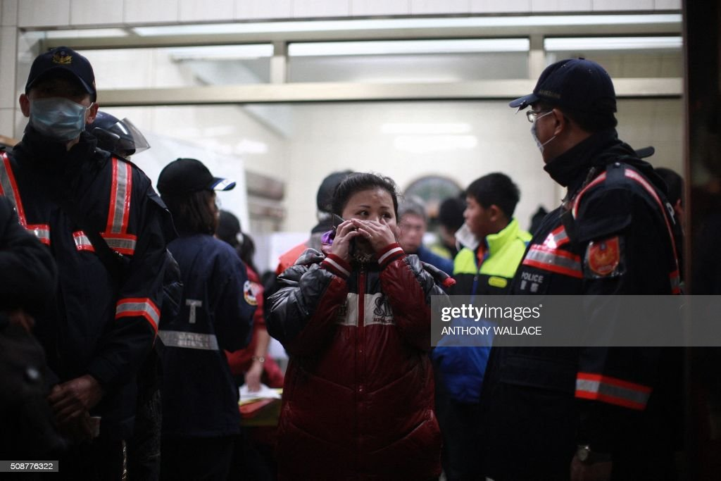 A woman (C) uses her phone as she walks out of an office set up to record numbers of missing persons and successful rescues, near the site of a collapsed building in the southern Taiwanese city of Tainan early on February 7, 2016 following a strong 6.4-magnitude earthquake. More than 250 people have been rescued from the Wei-kuan apartment complex in the southern city of Tainan since the quake hit at 4:00 am Saturday, killing 14 people and toppling four blocks of around 100 homes in total. WALLACE