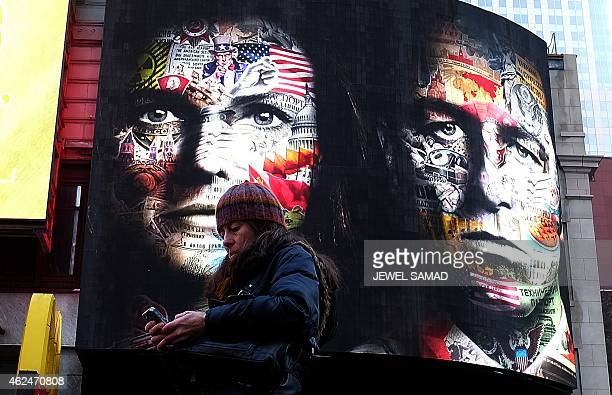 A woman uses her phone standing near an electric billboard advertising television show 'The Americans' in New York's Times Square on January 29 2015...
