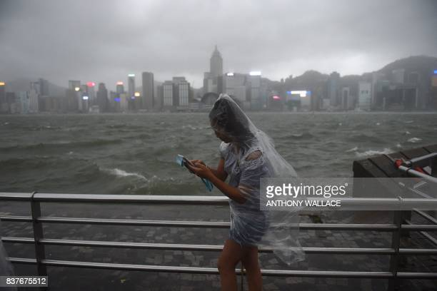 TOPSHOT A woman uses her phone while wearing a plastic poncho along Victoria Harbour during heavy winds and rain brought on by Typhoon Hato in Hong...