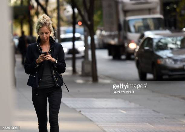 A woman uses her smart phone as she walks on 47th Street November 13 2014 in New York AFP PHOTO/Don Emmert