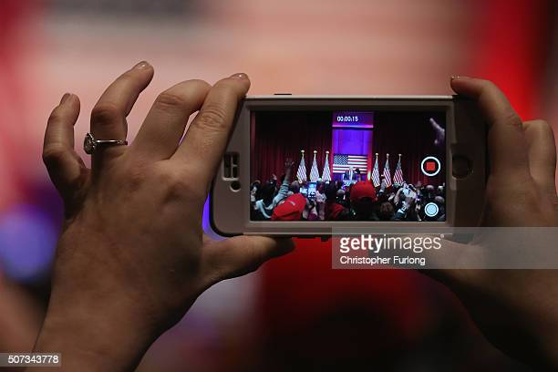 A woman uses her smart phone to photograph Republican presidential candidate Donald Trump as he speaks to veterans at Drake University on January 28...