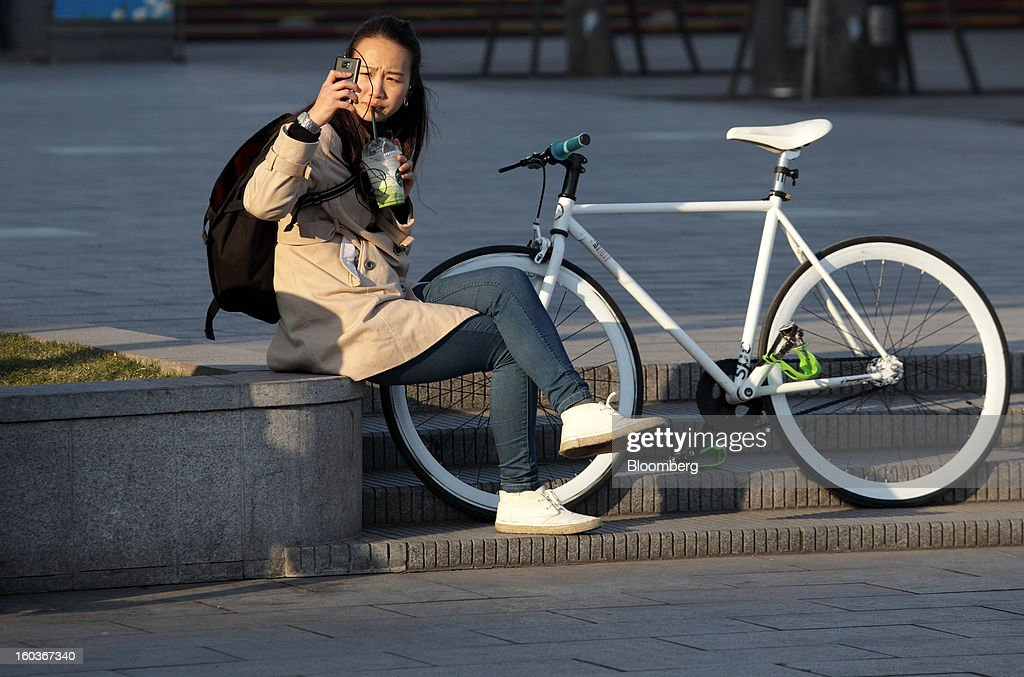 A woman uses her smartphone as she sits next to a bicycle on the Bund in Shanghai, China, on Monday, Jan. 28, 2013. China's economic growth accelerated for the first time in two years as government efforts to revive demand drove a rebound in industrial output, retail sales and the housing market. Photographer: Tomohiro Ohsumi/Bloomberg via Getty Images