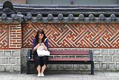 A woman uses her smartphone on a bench in Seoul on July 26 2016 South Korea's economy posted improved growth in the second quarter as exports and...