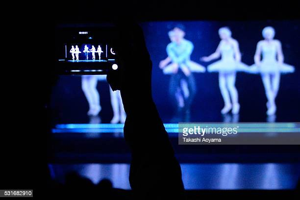 A woman uses her smartphone to take a video of a hologram show at the 'Hologram Dance Theater Celebrity and You' at the Madame Tussauds Tokyo on May...