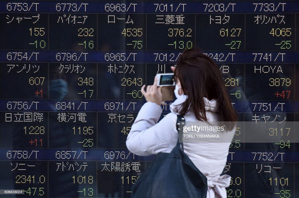 A woman uses her smartphone to take pictures of an electric quotation board flashing share prices of the Tokyo Stock Exchange (TSE) in front of a securities company in Tokyo on February 10, 2016. Tokyo stocks again dropped on February 10 to their lowest level since late 2014, as fears of a global recession hammered investor confidence ahead of testimony by the head of the US central bank. AFP PHOTO / Toru YAMANAKA / AFP / TORU YAMANAKA