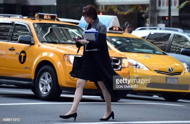 A woman uses her smartphone while crossing a street corner on November 13 2014 in New York AFP PHOTO/Don Emmert