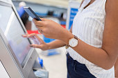 Unrecognizable young woman uses touch screen on kiosk to check in for flight in airport. She is holding a smartphone.