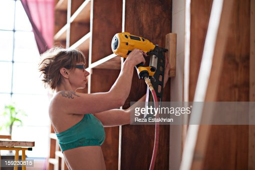 Woman uses power tools for carpentry : Foto de stock