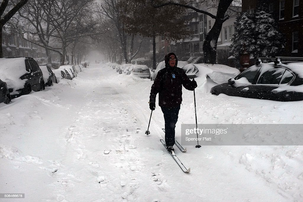 A woman uses skis to walk down a snow covered street on January 23 2016 in the Brooklyn borough of New York City The Northeast and parts of the South...