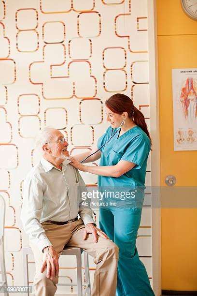 Woman uses stethoscope on man