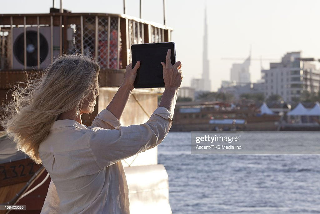Woman uses tablet to take picture, Dubai River : Stock Photo