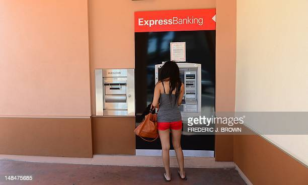 A woman uses the automated teller meachine at a branch of HSBC bank in Alhambra east of downtown Los Angeles on July 17 2012 in California...