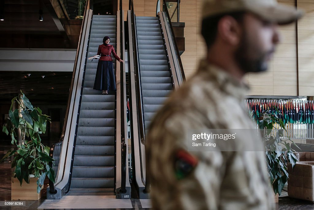A woman uses the escalator at the Libyan General National Congress in Tripoli as military guards keep watch in the lobby on March 10 2015 The seat of...