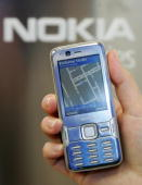 A woman uses the navigate tool on the Nokia N82 cell phone with an internal GPS receiver and Nokia map at the CeBIT technology fair the first day the...