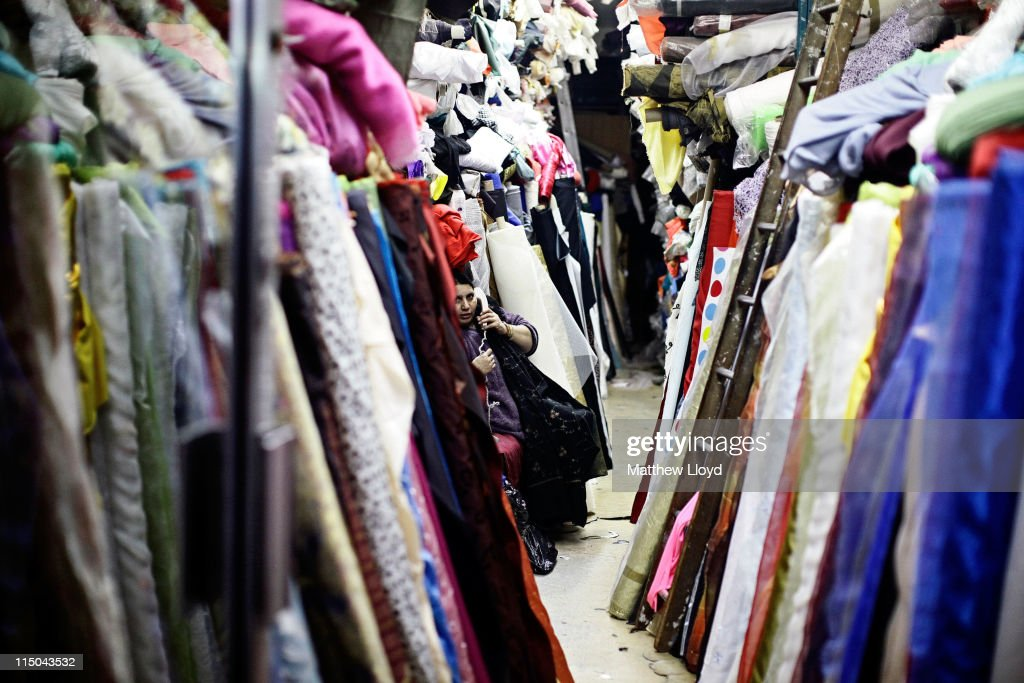A woman uses the phone in her linen and fabric shop on Brick Lane, on October 30, 2010 in London, England. The East End of London is home to a thriving art community, with paintings, sculptures and other works covering walls, buildings and rooftops across the area.