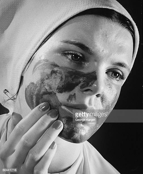 A woman using a beauty care skin product on her face