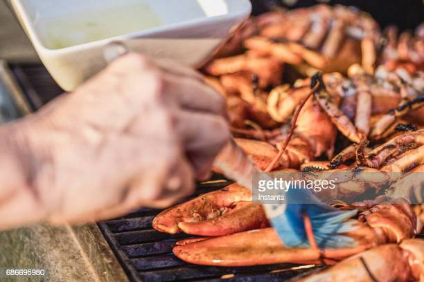 Woman, using a brush, is basting Canadian lobsters with olive oil to grill them on the barbecue.