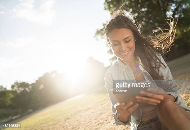 Woman using a digital tablet at the park