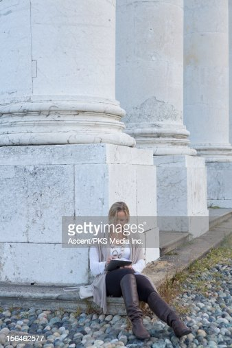 Woman using a digital tablet by a marble column : Stock Photo