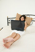 Woman using a laptop on the bed