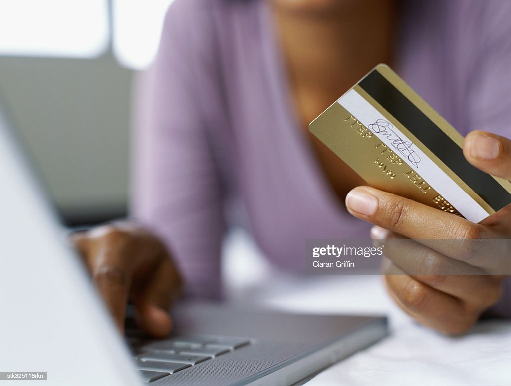 woman using a laptop while holding a credit card : Stock Photo