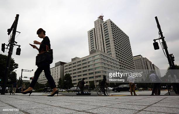 A woman using a mobile phone walks through the Kasumigaseki area of Tokyo Japan on Thursday Sept 11 2014 Losing women from the workforce in their 20s...