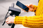 A woman in a yellow sweater using a smart phone while gripping the handlebars of an electric scooter in the street.