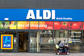 A woman using a motorized cart sits outside the entrance to an Aldi supermarket store in London UK on Monday June 29 2015 The growth of Aldi and...