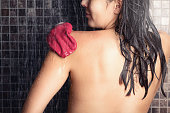 Woman with wet hair standing using a peeling glove in a shower rubbing her shoulder to remove dead cells and rejuvenate her skin in a personal hygiene, skincare and beauty concept, view from behind