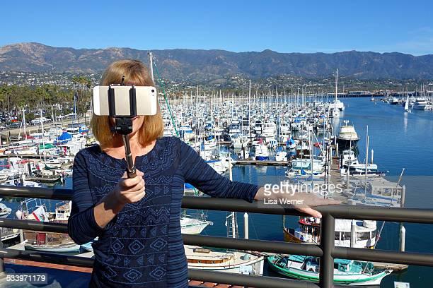 Woman using a selfie stick to take a self portrait in Santa Barbara California