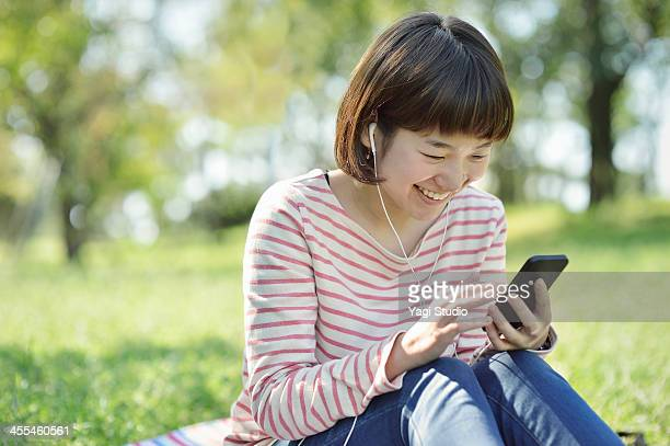 Woman using a Smart phone in the green