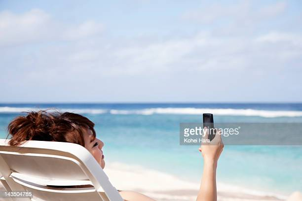 woman using a smart phone on the beach