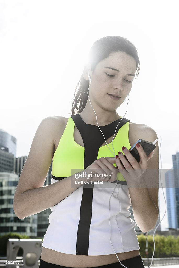 A woman using a smartphone exercising in the city : Stock Photo