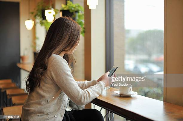 Woman using a smartphone in a cafe