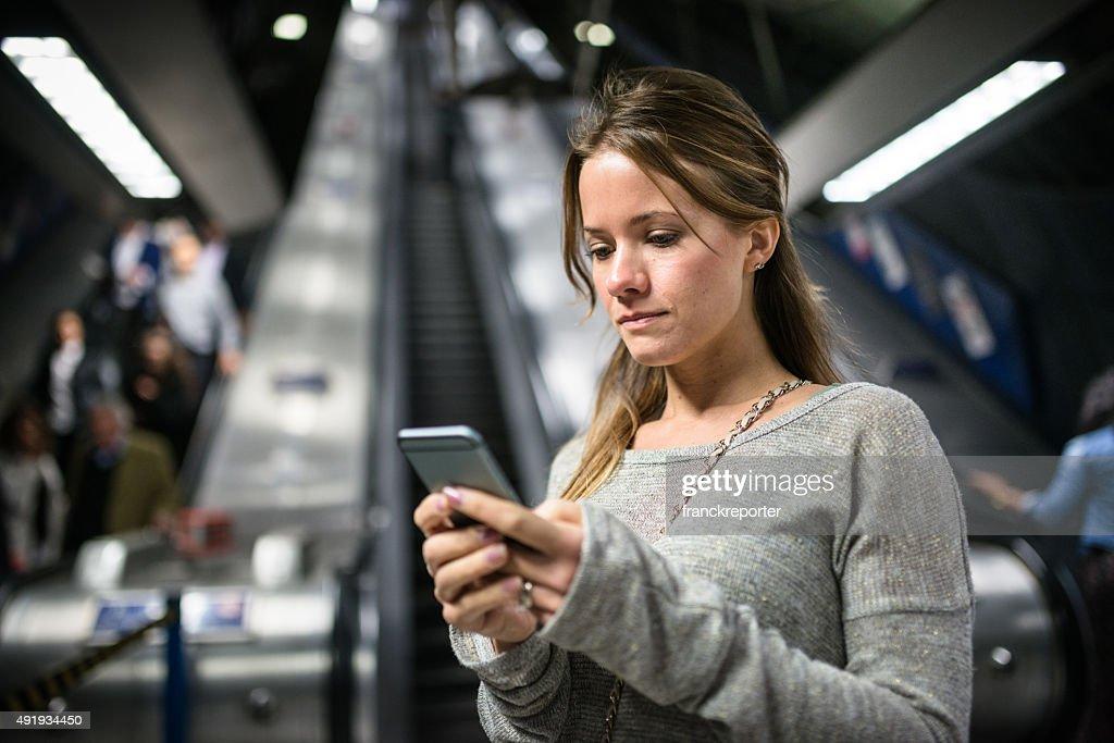 Frau, die einen smartphone auf der U-Bahn-station : Stock-Foto